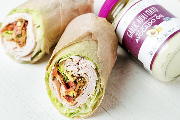Turkey Club Lettuce Wrap wrapped in parchment paper next to Primal Kitchen Garlic Aioli Mayo