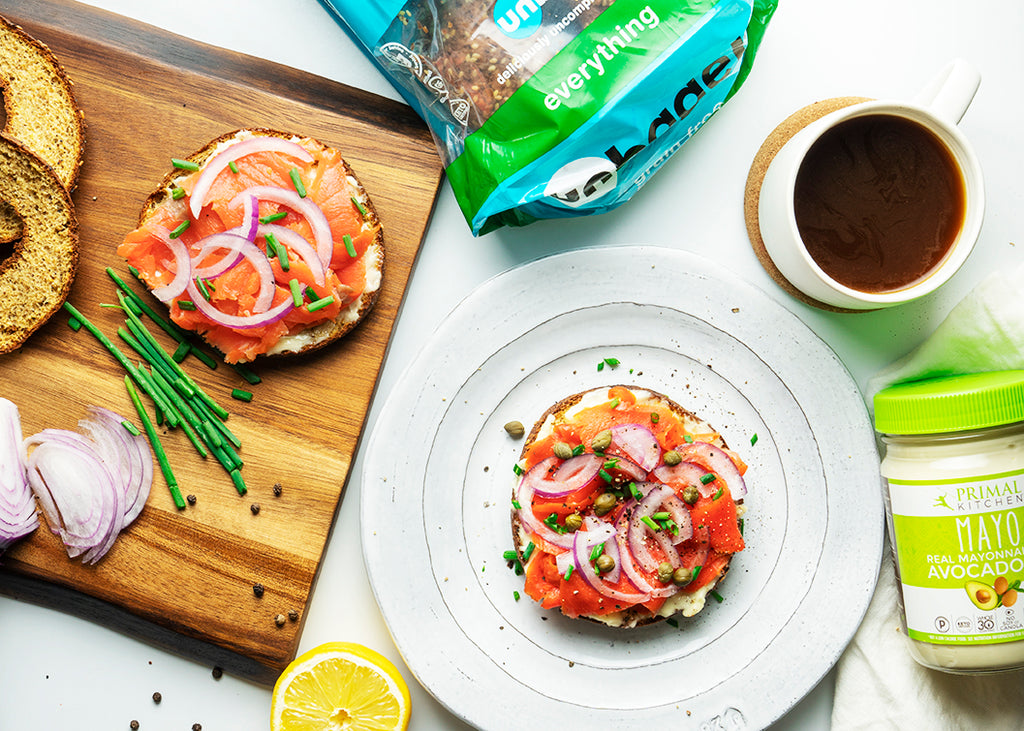 An overhead shot shows a white plate with a smoked salmon breakfast bagel, mayo, unbun bagels, and a cutting board with ingredients.