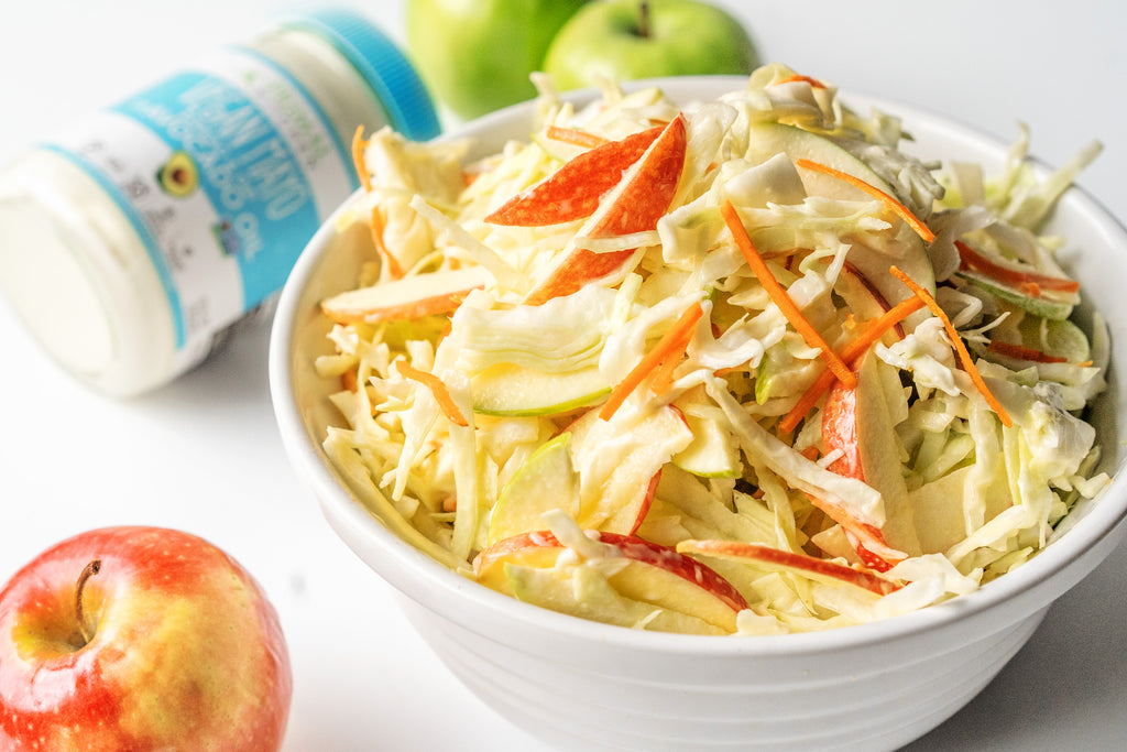 Vegan Apple Coleslaw in a big white bowl with a red apple next to it