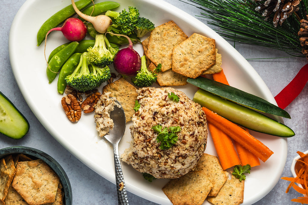 Vegan cheese ball on a white platter with a silver spoon scooping some of the cheese. Also on the plate: broccoli florets, radishes, snap peas, carrot and cucumber sticks, and crackers.