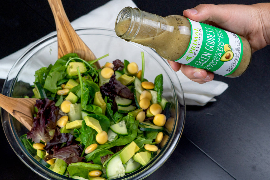 Vegetarian Green Salad with a hand pouring on Primal Kitchen Green Goddess Dressing into the bowl