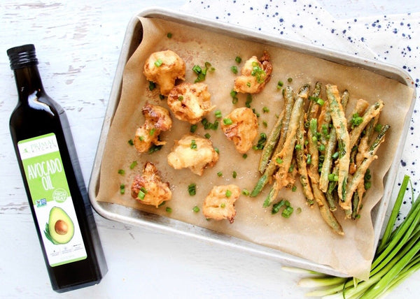 Cauliflower and green bean tempura on a baking sheet with parchment paper