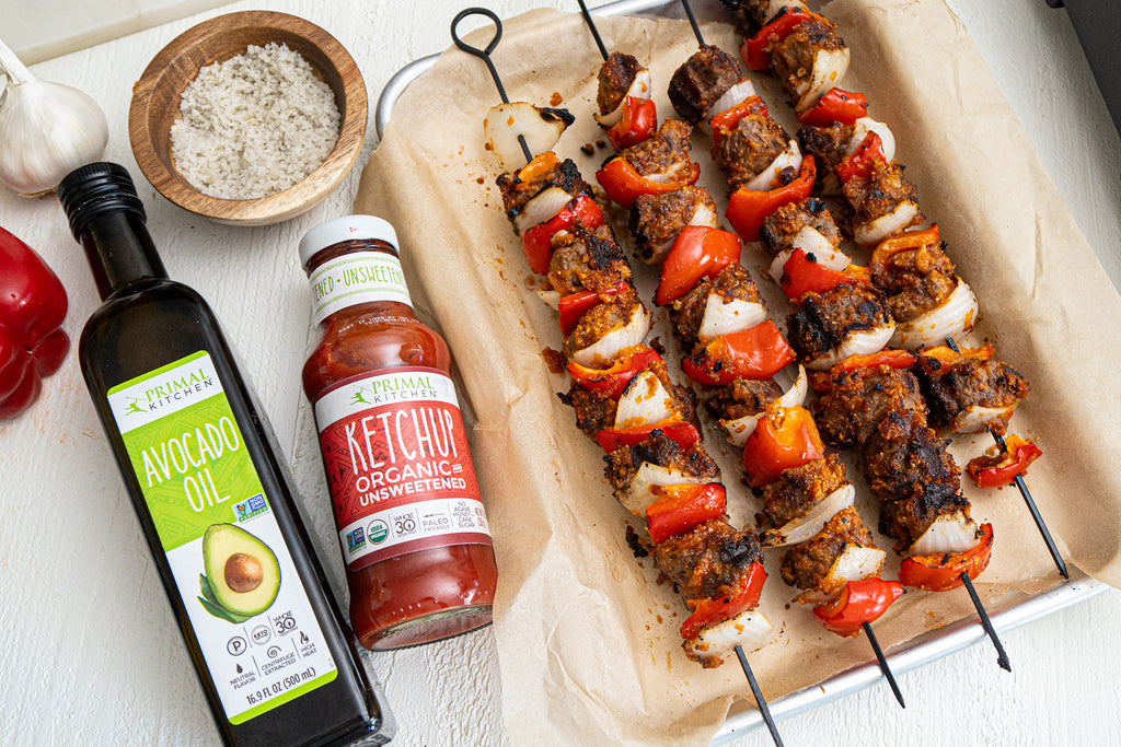 Four West African Steak Kabobs lay on a pan lined with parchment next to an avocado oil bottle, ketchup bottle and small wooden bowl of salt.