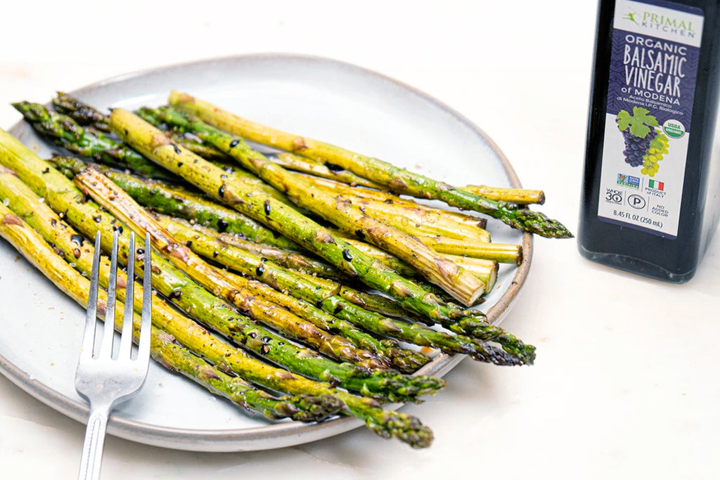 Roasted asparagus with balsamic vinegar on a white plate with a fork