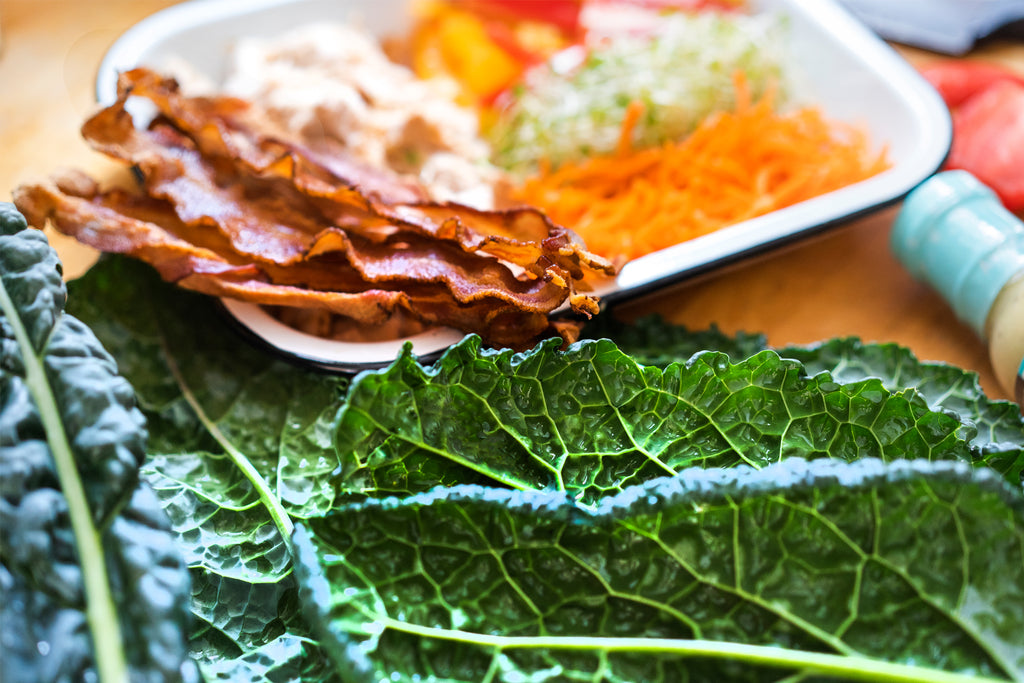 Collard green leaves with chicken bacon wrap ingredients on a white plate in the background