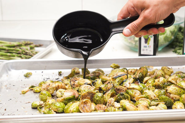 Brussels sprouts on a sheet pan being drizzled with balsamic reduction