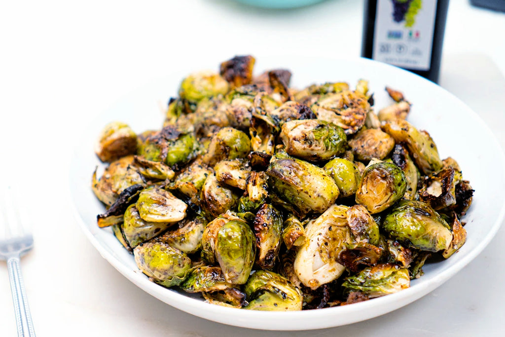 Roasted Brussels sprouts with balsamic glaze on a white plate