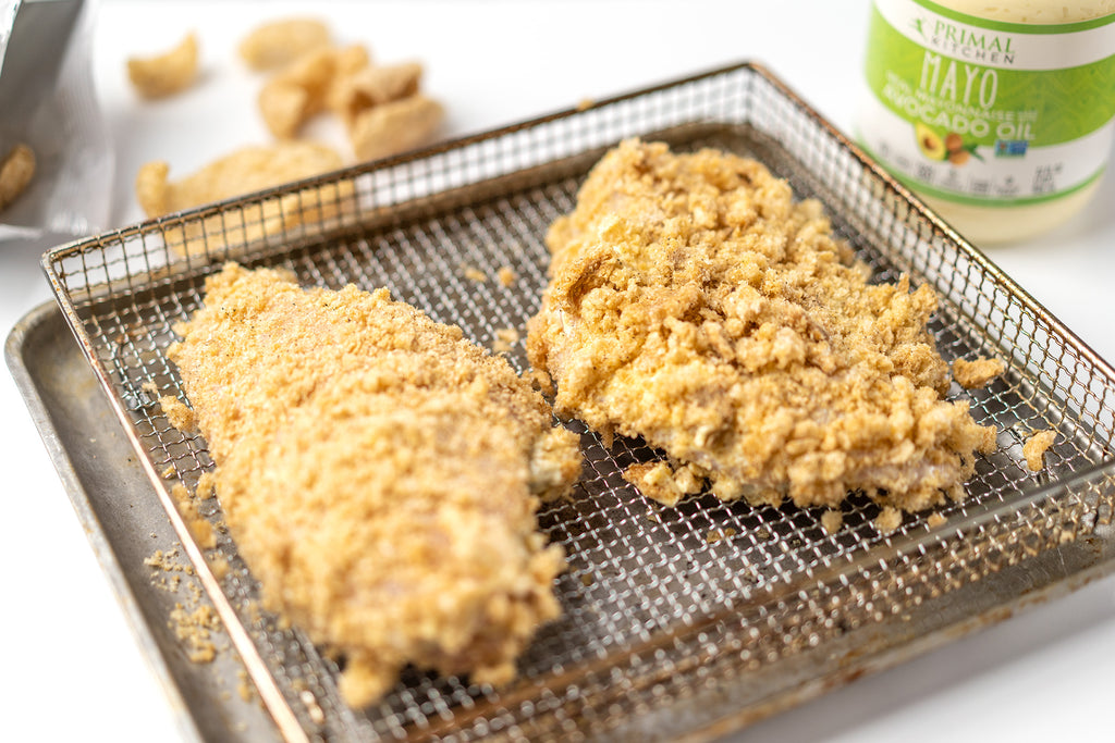 Stuffed chicken breasts with pork rind crumbs on a sheet pan