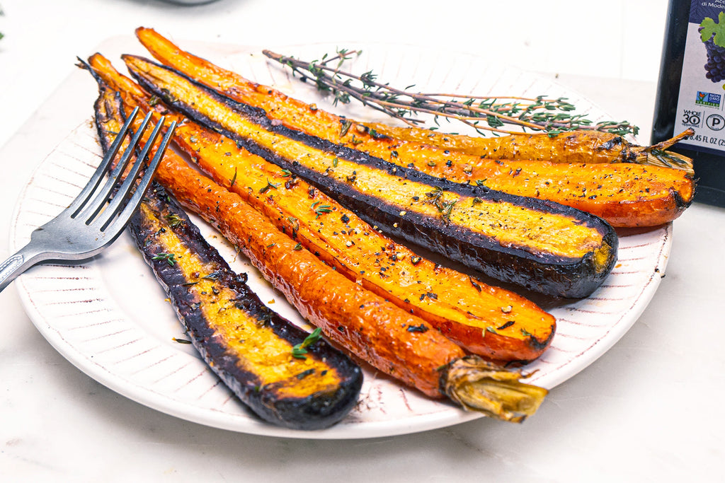 Roasted carrots with balsamic vinegar and thyme on a white plate