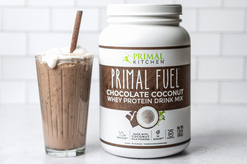 Chocolate milkshake in a glass with a metal straw next to Primal Fuel Chocolate