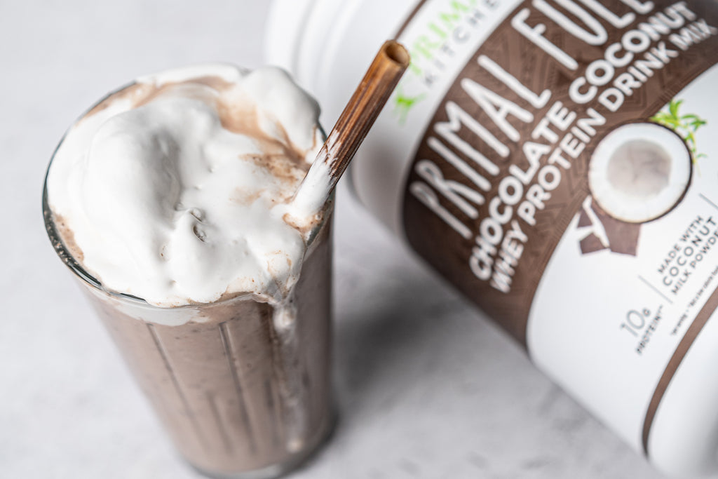 Chocolate milkshake in a glass with a metal straw next to container of Primal Kitchen Primal Fuel Chocolate