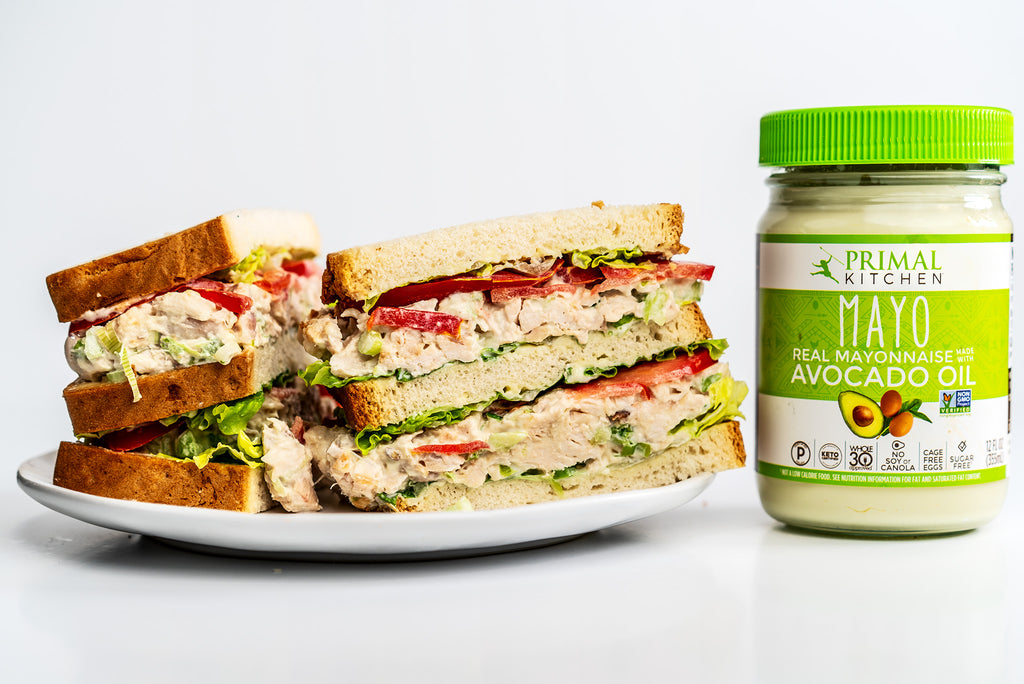 A classic chicken salad sandwich is stacked on a white plate next to mayo.