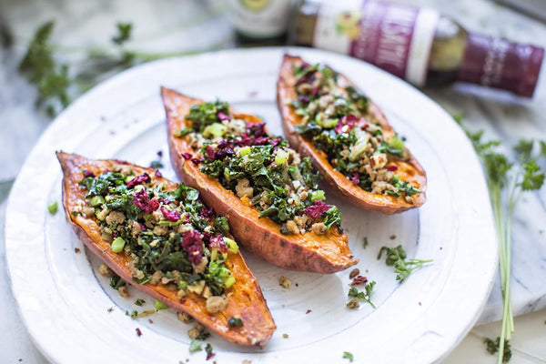 Roasted sweet potatoes stuffed with cranberries and ground turkey on a white plate