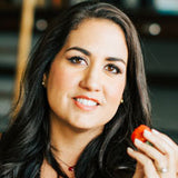 headshot of Cristina Crup holding a strawberry