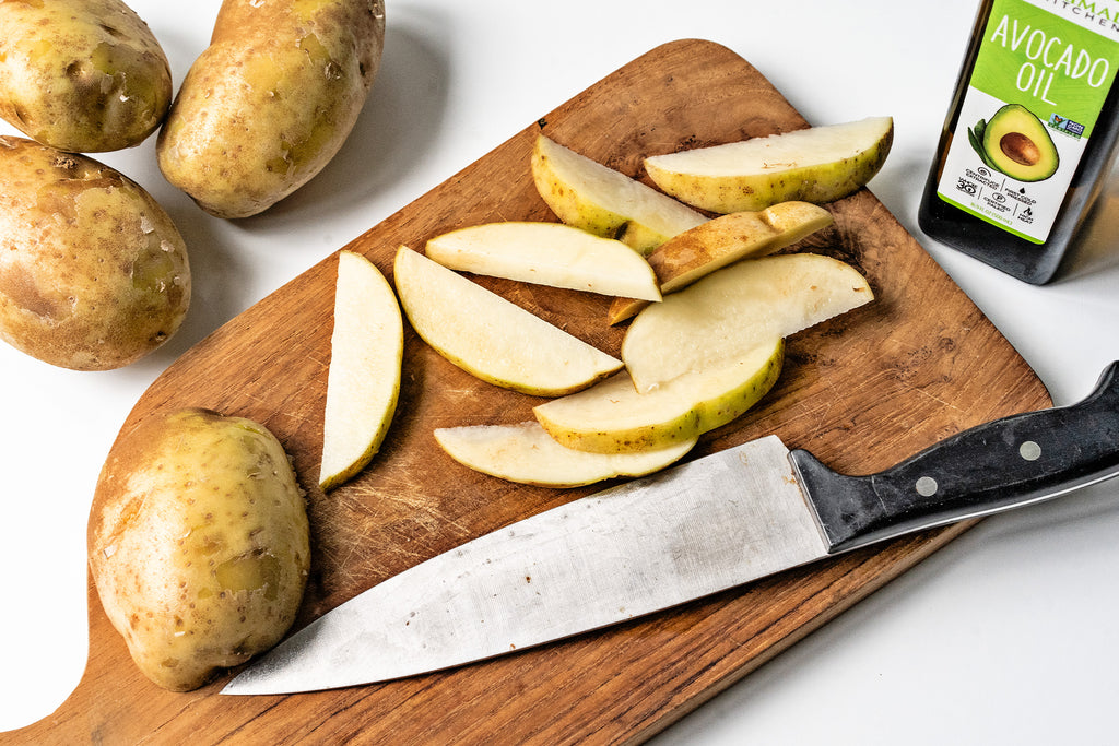 Sliced potato wedges on a wood cutting board with a chef's knife