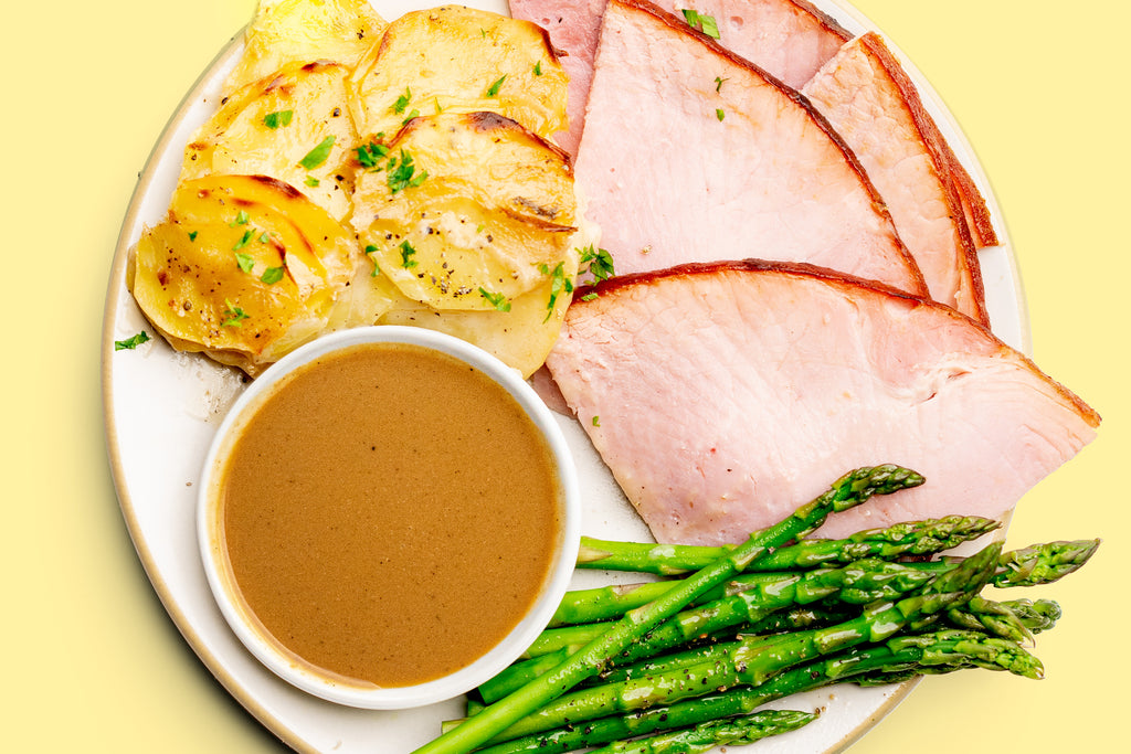 A white plate filled with sliced ham, steamed asparagus, scalloped potatoes, and Primal Kitchen Ham Glaze in a white ramekin.
