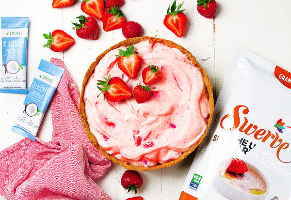 Keto strawberry cream pie with strawberries on top next to Primal Kitchen Collagen Fuel vanilla packets and a package of Swerve
