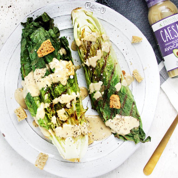 Grilled Caesar salad with Primal Kitchen Caesar Dressing and croutons on a white plate