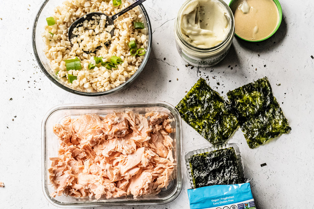 Keto spicy salmon hand roll ingredients: cooked flaked salmon in a container, SeaSnax nori sheet, Primal Kitchen Jalapeno Lime Vegan Mayo, and a bowl of cauliflower rice with green onions
