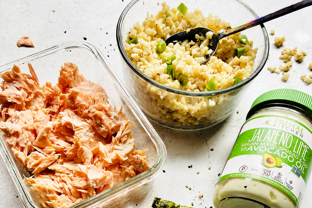 A bowl of cauliflower rice with diced green onions with a spoon in it with a container of cooked, flaked salmon. A jar of Primal Kitchen Jalapeno Lime Mayo next to these.