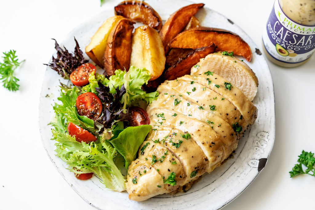 Sliced baked chicken breast, side green salad, baked sweet potato and apple wedges on a white plate