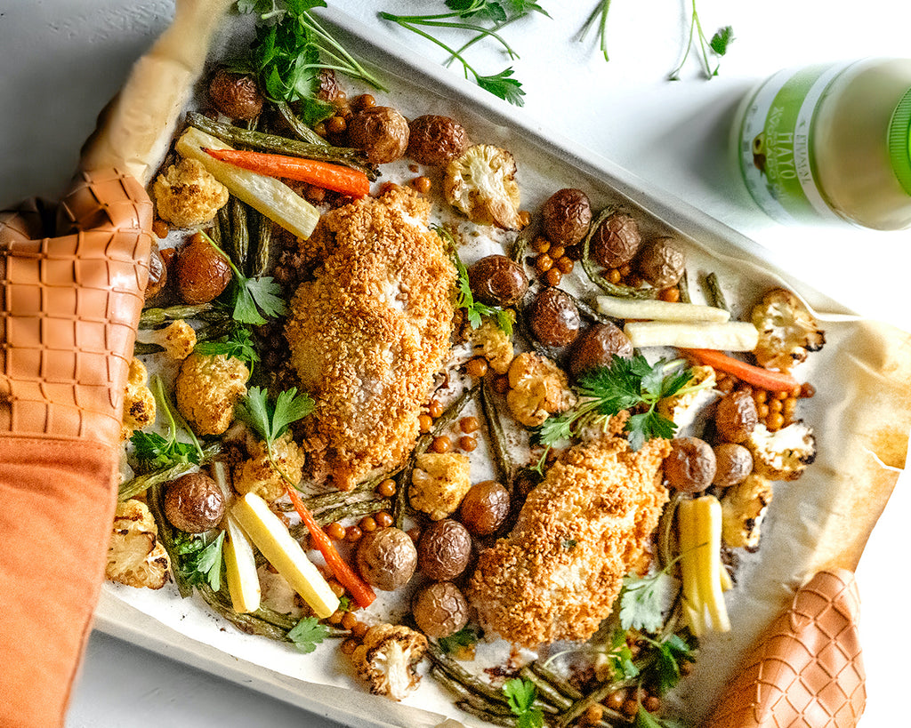 Orange oven mitts are holding a sheet pan with Parmesan crusted chicken and veggies, with Primal Kitchen Mayo in the background.