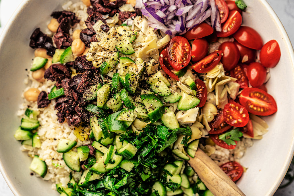 Close up shot of Keto Vegan Mediterranean Bowl before being tossed. Large white bowl filled with cauliflower rice, an avocado cut in half, sliced cherry tomatoes, chopped olives, chopped parsley, sliced red onions, chickpeas, chopped artichoke hearts, diced cucumbers, chopped pepperoncinis, and dressed with Primal Kitchen Avocado Oil & Vinegar Vinaigrette.