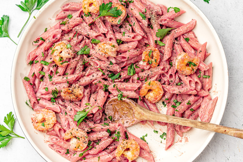 Overhead shot of penne with pink sauce and shrimp in a large white bowl with a wooden spatula. Penne is topped with chopped parsley.