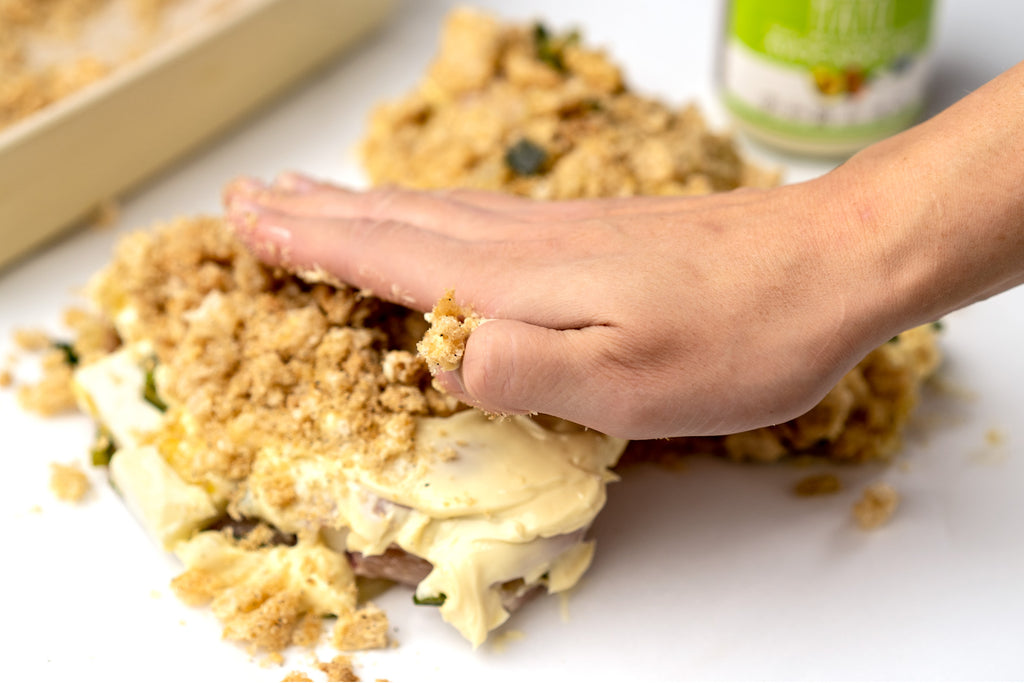 Hand pressing pork rinds into stuffed chicken breast spread with mayo with avocado oil