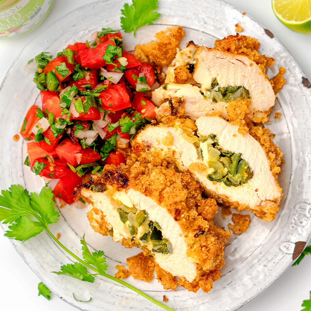 Keto Tex-Mex Stuffed Chicken breast sliced on a white plate with a side of pico de gallo and cilantro leaves scattered on top