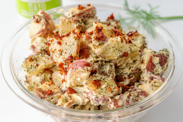 Potato salad with mayo and bacon in a large clear bowl