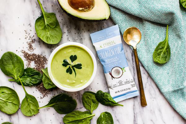 Kelly LeVeque's Fab Four Smoothie with Avocado and Primal Fuel Collagen Fuel Vanilla next to spinach leaves and a green napkin