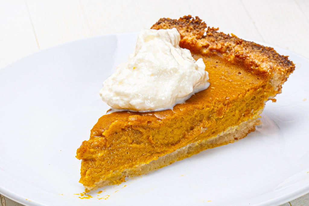 pumpkin pie with whipped cream on a white plate