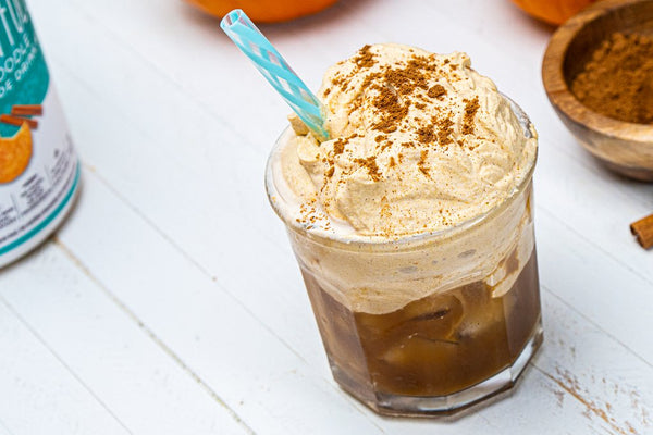 Whipped pumpkin coffee in a glass with a blue straw