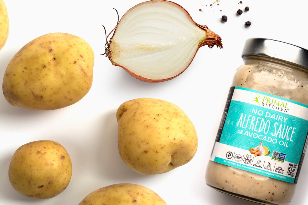 Baby yukon gold potatoes with a sliced white onion and a jar of Primal Kitchen No Dairy Alfredo Sauce