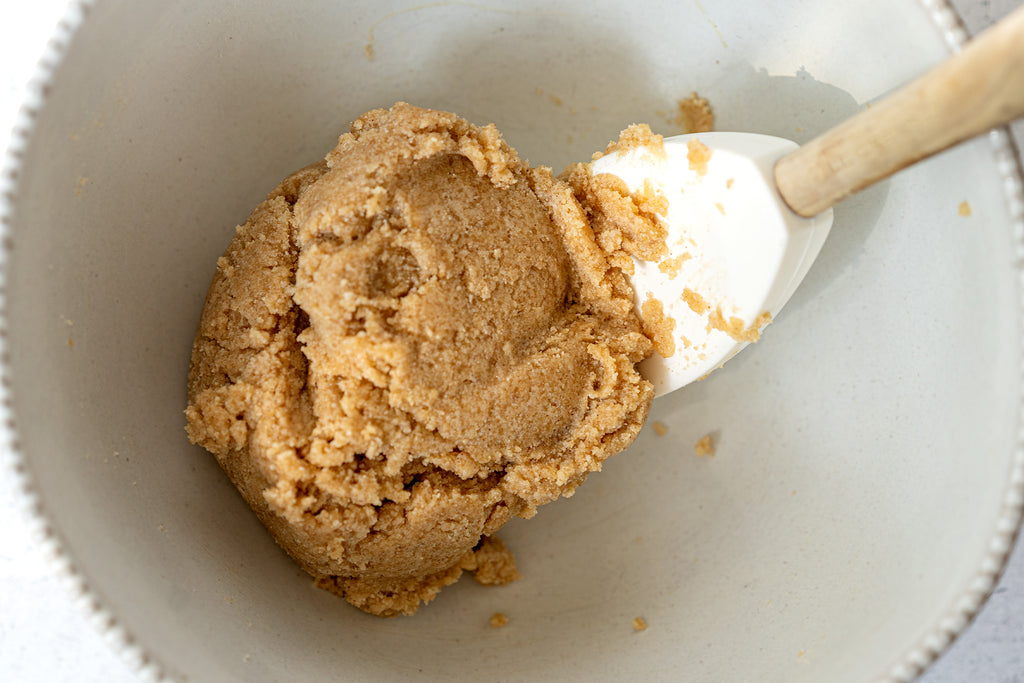 Snickerdoodle cookie dough in a white bowl being stirred by a white spatula
