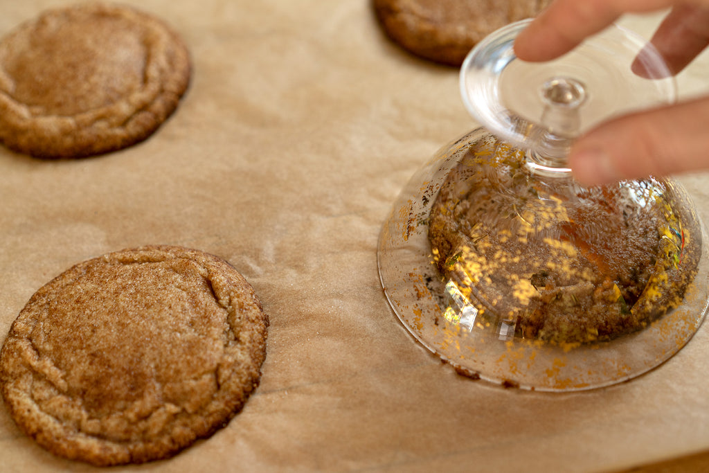 Hand using an upside down glass to shape the snickerdoodle cookies