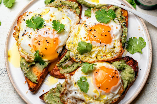 Sweet potato toast with avocado and egg on a white plate