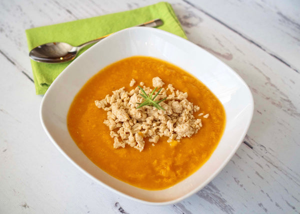 Sweet potato soup in a white bowl topped with ground turkey