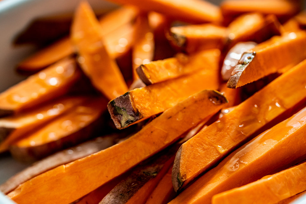 A closeup of airfryer sweet potato fries shows them coated in avocado oil and ready to fry!