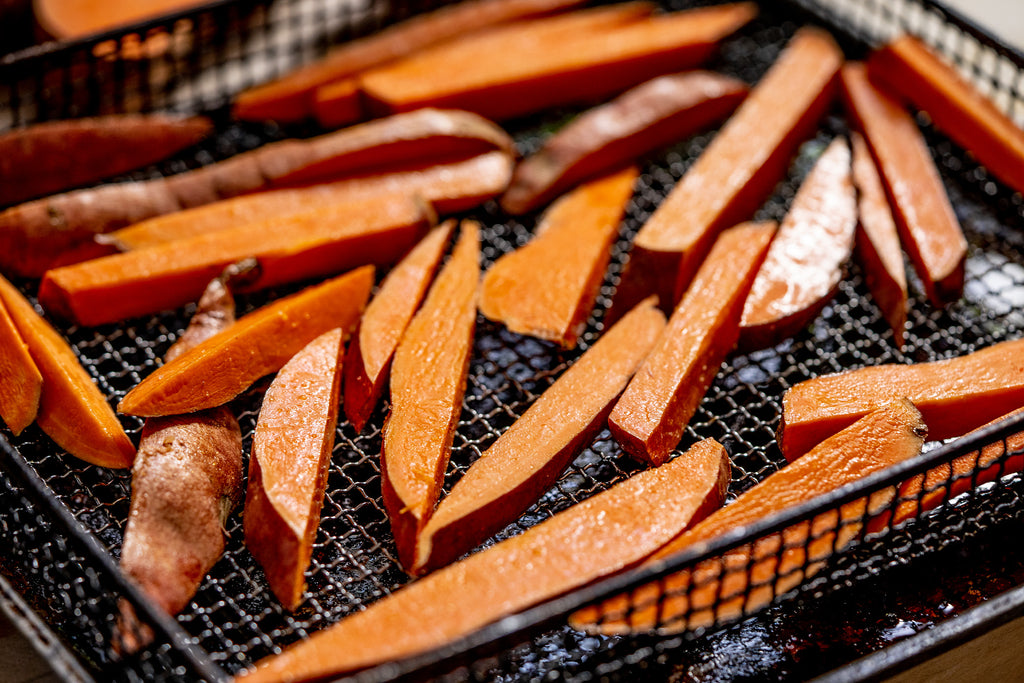 AirFryer sweet potato fries sizzle in the basket, ready to be fried.