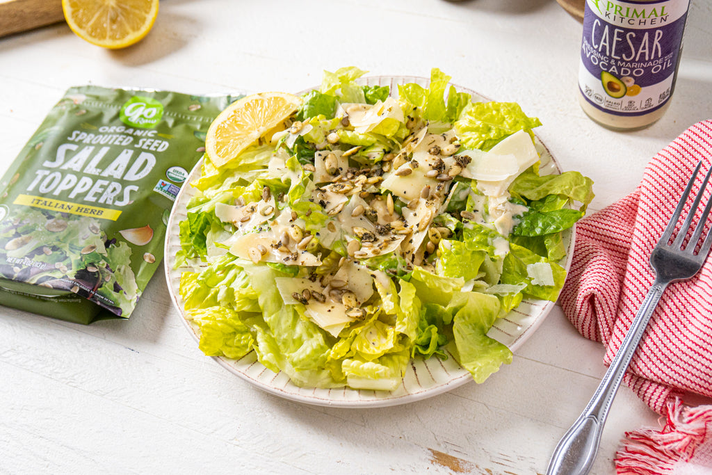Caesar salad on a white plate next to a silver fork. Go Raw sprouted seed bag and Primal Kitchen Caesar Dressing are next to the salad.
