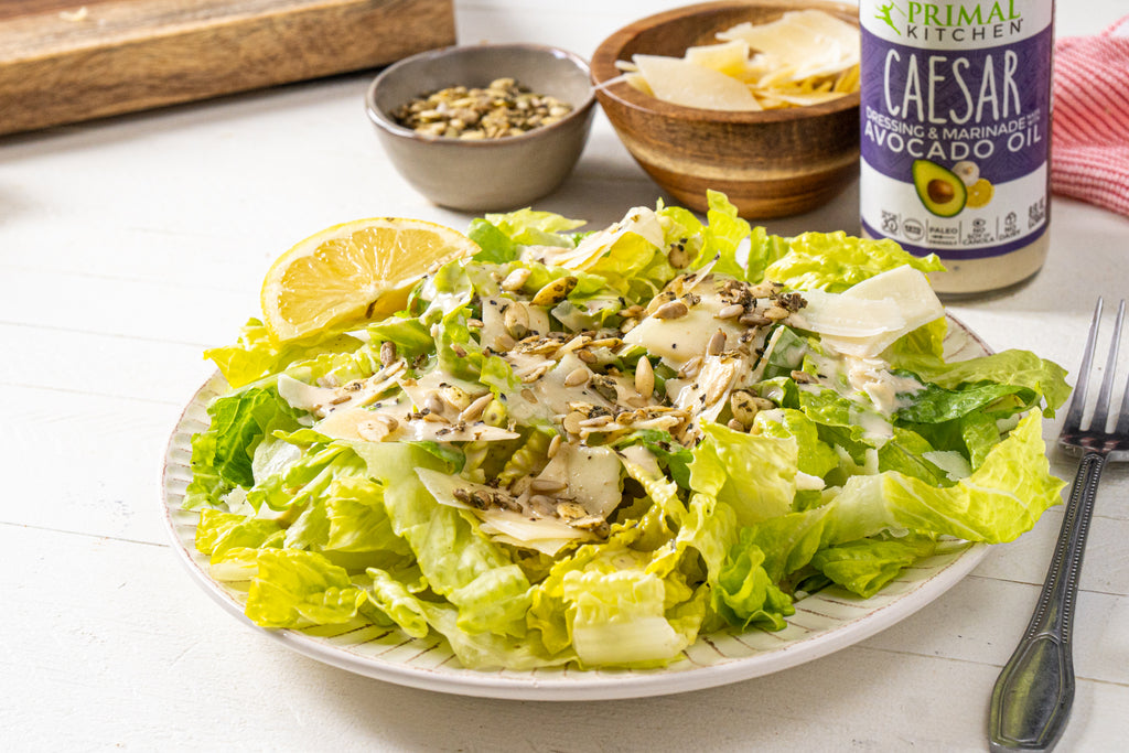Caesar salad with Go Raw sprouted seeds and parmesan curls on top. A silver fork is next to the salad plate, along with a bowl of parmesan curls, sprouted seeds, and Primal Kitchen Caesar Dressing.