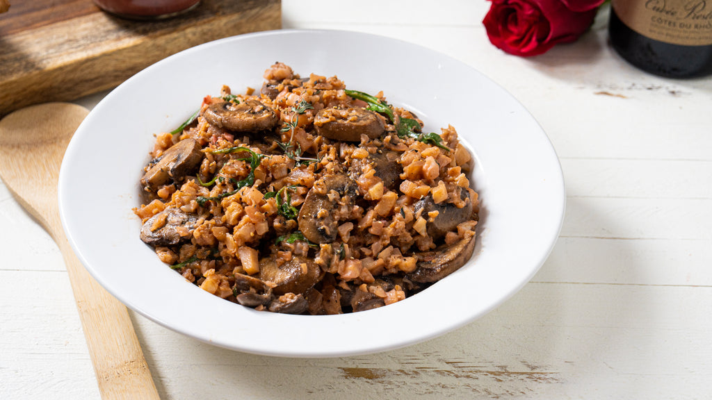 Cauliflower risotto with mushrooms on a large white dinner plate. A wooden spoon is next to the plate.
