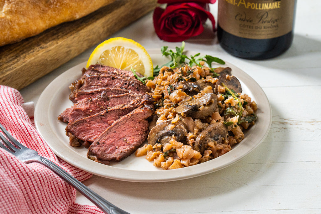 Cauliflower and mushroom risotto with sliced steak on a white plate with fresh herbs and a slice of lemon