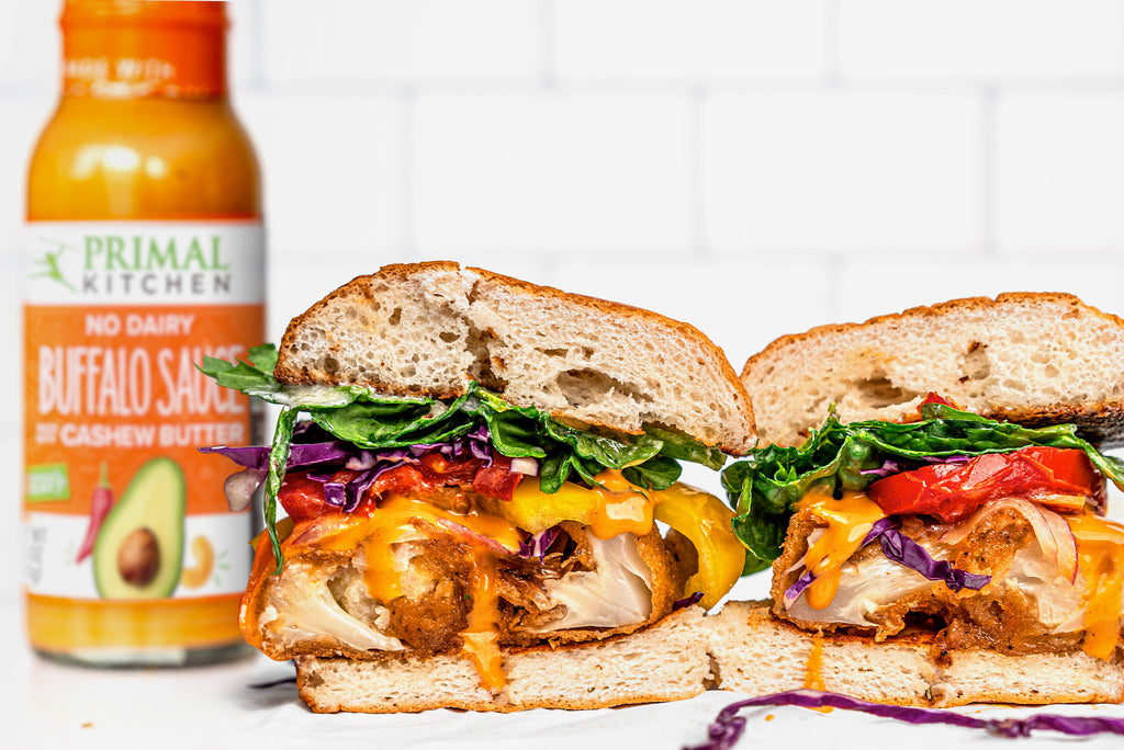 A sliced vegan buffalo cauliflower sandwich sits next to a bottle of buffalo sauce on a white table with a white backdrop.
