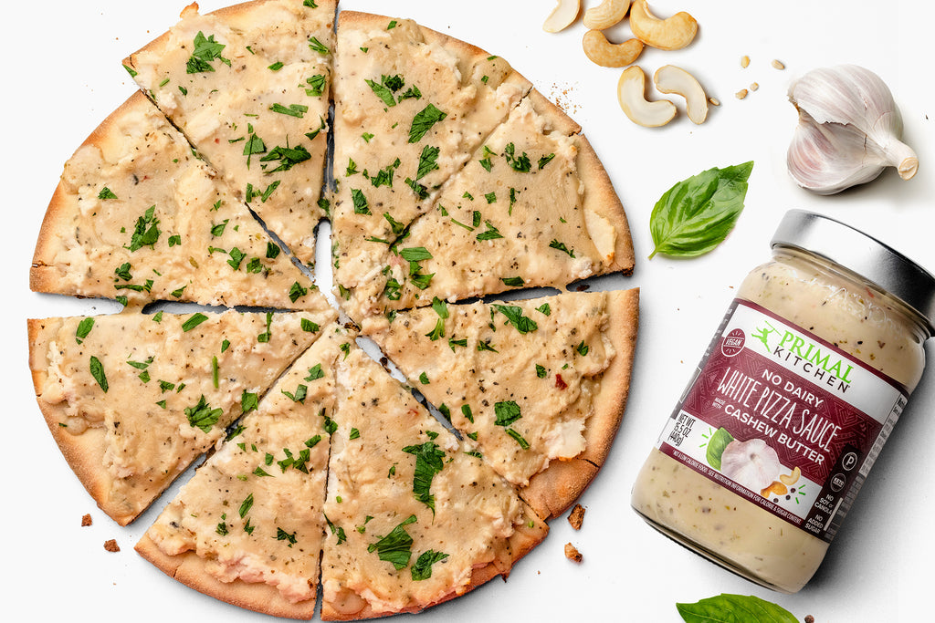 Grain free crust is topped with no dairy white pizza sauce to make vegan white pizza, with a jar and ingredients nearby.