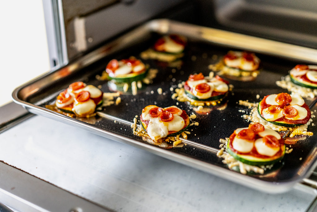 Zucchini Pizza Bites are coming out of the air fryer oven on a silver tray.