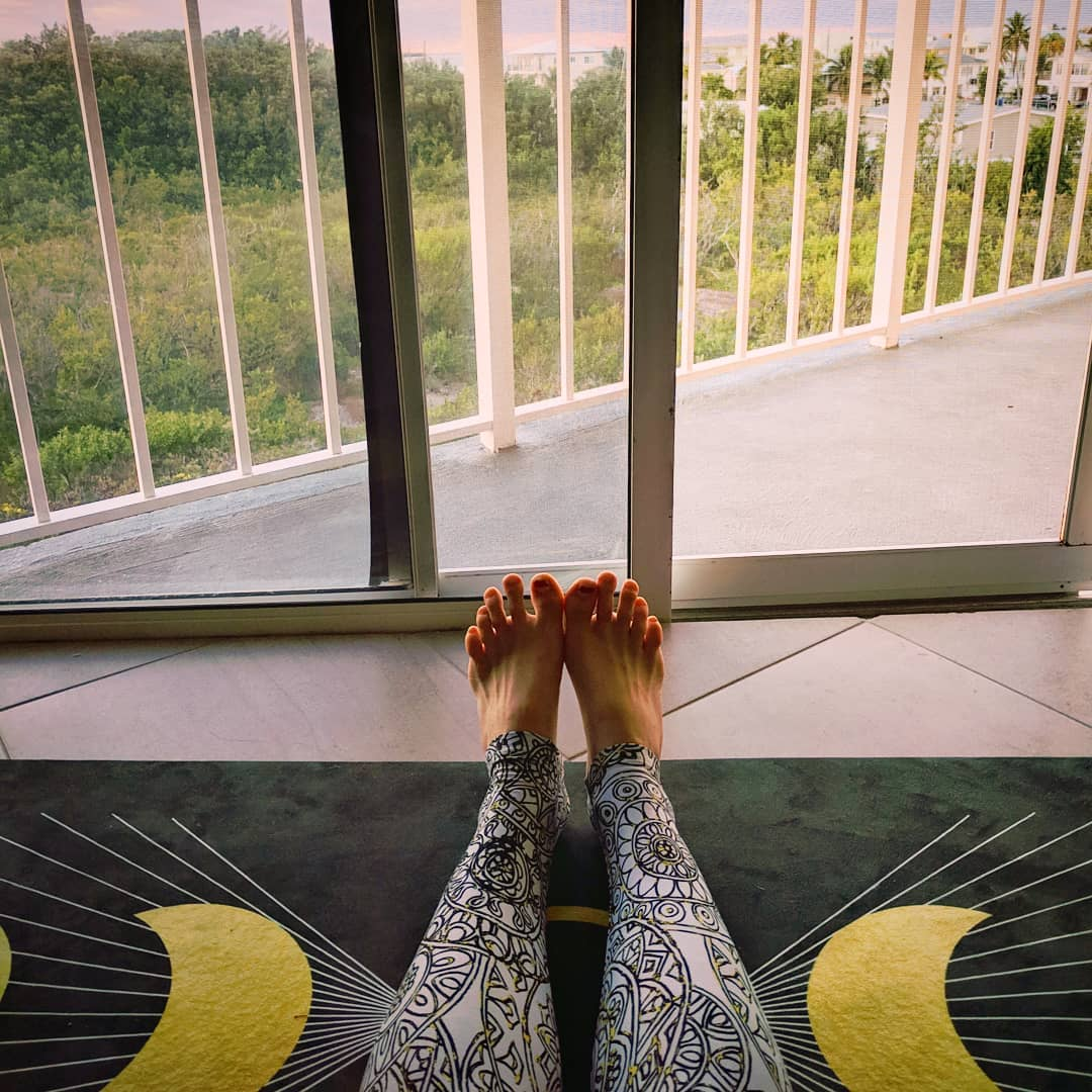 Legs stretched out on a 'Waxing Crescent Phases of the Moon' Big Raven Yoga mat