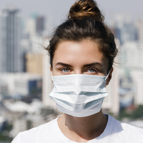 Beautiful woman wearing non-surgical mask with city background.